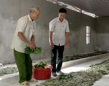 Ông Hà Đức Nhận (bên trái) giới thiệu với lãnh đạo xã về mô hình nuôi tằm.
