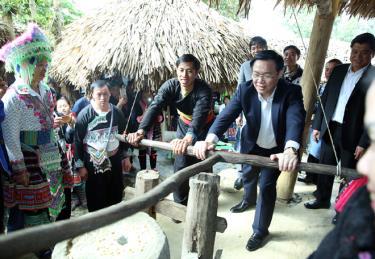Phó Thủ tướng Vương Đình Huệ tham gia trải nghiệm xay gạo ở chợ người Mông, bản Sin Suối Hồ, Lai Châu.
