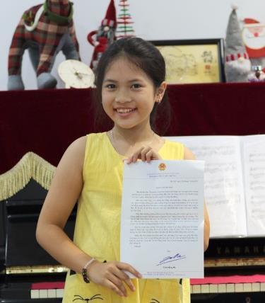 Em Nguyệt Linh cùng bức thư của Bộ trưởng Trần Hồng Hà.
