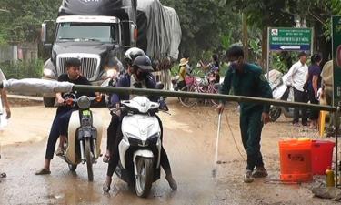 Lực lượng chức năng phun thuốc tiêu độc khử trùng các phương tiện đi qua vùng dịch tại xã Quy Mông.