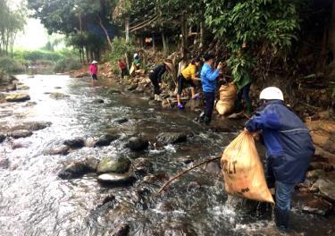 Thanh niên tình nguyện vớt rác dưới lòng suối xã Việt Hồng.