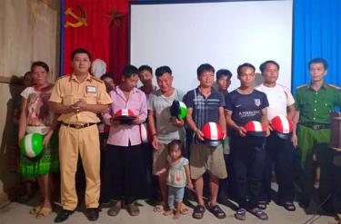 Cán bộ Đội Cảnh sát giao thông trật tự, Công an huyện Trấn Yên trao mũ bảo hiểm cho các hộ nghèo thôn Khe Tiến, xã Hồng Ca.