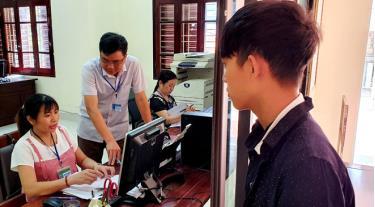 Cán bộ Chi cục Thuế khu vực Nghĩa Văn - Trạm Tấu tuyên truyền, hướng dẫn nhân dân đăng ký thuế, kê khai, hoàn thuế.