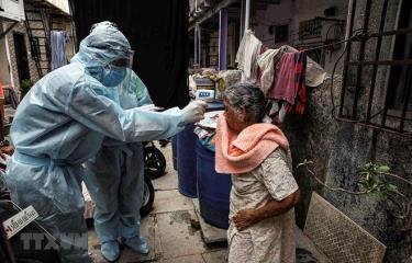 Nhân viên y tế lấy mẫu xét nghiệm COVID-19 cho người dân ở Mumbai, Ấn Độ ngày 17/6/2020.