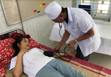 Cán bộ Trạm Y tế xã Nghĩa Lợi chăm sóc sức khỏe ban đầu cho người dân.