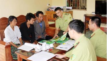 Cán bộ kiểm lâm huyện Trấn Yên tuyên truyền, ký cam kết bảo vệ rừng, phòng cháy chữa cháy rừng tới các hộ dân.