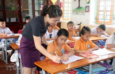 Giáo viên tiểu học hướng dẫn học sinh làm bài tập.