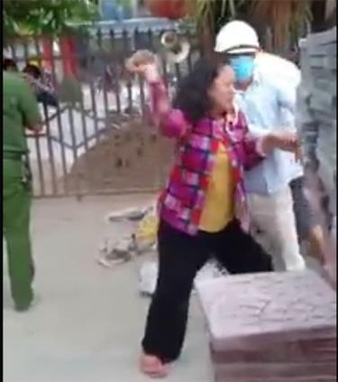 Ảnh cắt từ clip bà Chiến cầm gạch ném lực lượng thực thi công vụ.