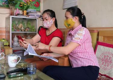 Cán bộ phường Minh Tân, thành phố Yên Bái tuyên truyền, hướng dẫn người dân cài ứng dụng Bluezone trên điện thoại thông minh.