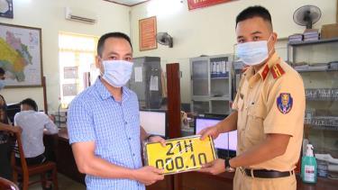 Cán bộ Phòng Cảnh sát giao thông, Công an tỉnh Yên Bái trao biển vàng cho chủ phương tiện kinh doanh vận tải khách.