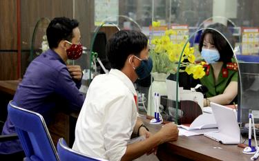 The staff of the public administrative service centre and visitors to the centre wear face masks. (photo: Thu Trang)