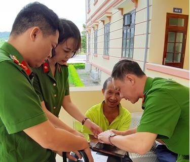 Cán bộ chiến sĩ công an thuộc Trung tâm Phục vụ hành chính công tỉnh hỗ trợ người khó khăn thực hiện thủ tục cấp chứng minh nhân dân.