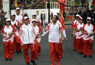 Tổng thống Indonesia Joko Widodo (giữa) cầm ngọn đuốc Thế vận hội châu Á và Bộ trưởng Thanh niên và Thể thao Imam Nahrawi (trái) trong buổi lễ Ngày Độc lập tại Cung điện Merdeka ở Jakarta, ngày 17/8/2018.