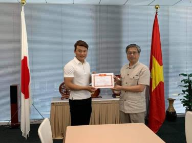 Tổng Lãnh sự Việt Nam tại Fukuoka Vũ Bình trao tặng Giấy khen cho anh Vũ Đức Huỳnh.