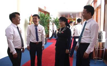 Đại biểu Triệu Văn Huấn và Phan Thị Trung Kiên (đứng giữa) - Đoàn đại biểu Đảng bộ huyện Lục Yên trao đổi với các đại biểu về dự Đại hội.