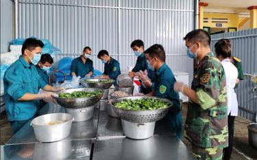 Các chiến sĩ dân quân chuẩn bị bữa ăn trong Khu cách ly Trường Phổ thông Dân tộc nội trú Trấn Yên.