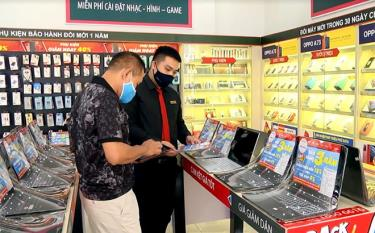 Nhân viên Cửa hàng FPT tại thành phố Yên Bái tư vấn sản phẩm máy tính xách tay cho khách hàng.