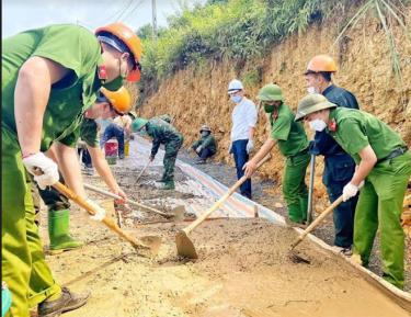 Cán bộ, chiến sĩ Công an huyện Văn Chấn tham gia cùng dân làm đường giao thông tại các thôn bản vùng cao.