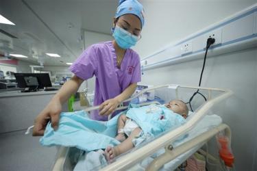 Nhân viên y tế chăm sóc trẻ mới sinh tại bệnh viện ở tỉnh Quý Châu (Trung Quốc), ngày 11/5/2021. (Ảnh: AFP/TTXVN)