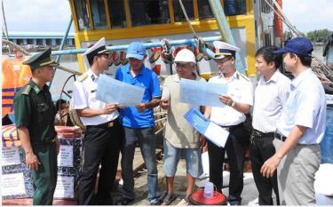 Cán bộ Vùng 2 Hải quân phát tờ rơi tuyên truyền Chỉ thị 45 của Thủ tướng Chính phủ cho ngư dân.