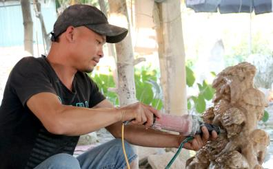 Hoang Xuan Khuc works on a stone statute.